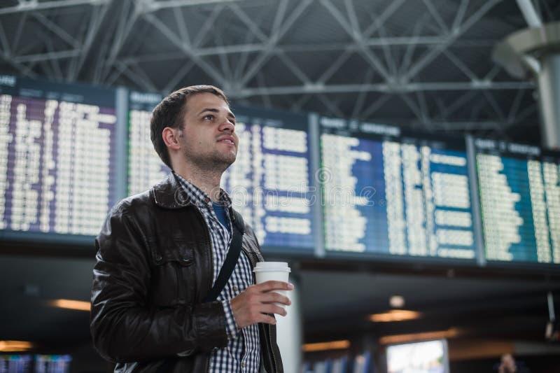 Ung man med en påse i flygplats nära den hållande koppen kaffe för flygschema royaltyfria foton