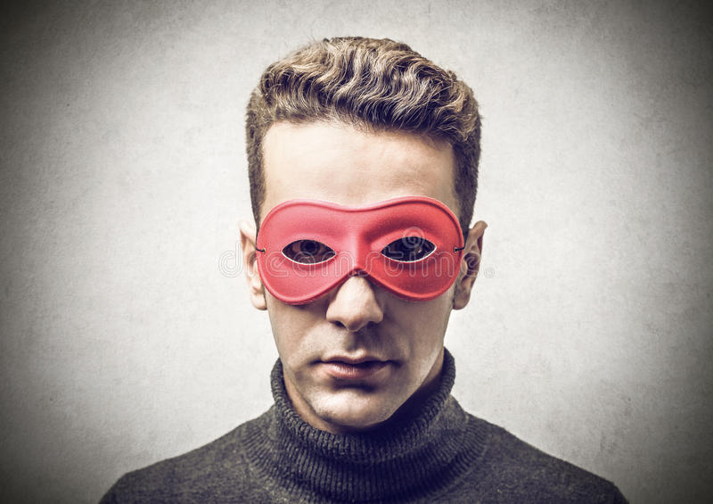 Ung man med en röd maskering arkivbilder