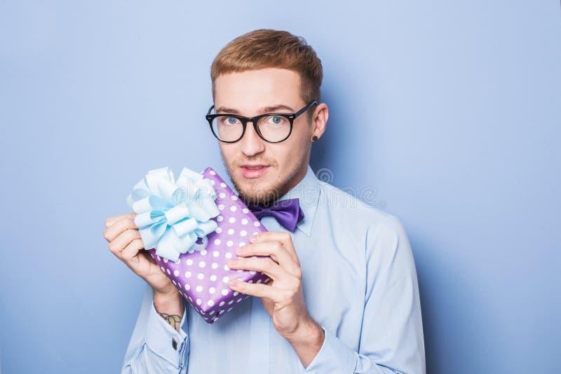 Ung man med en slågen in gåvaask Gåva födelsedag, valentin royaltyfri foto