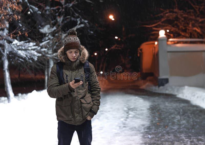 Ung man med en telefon i en stadsgata i en frostig afton royaltyfri foto