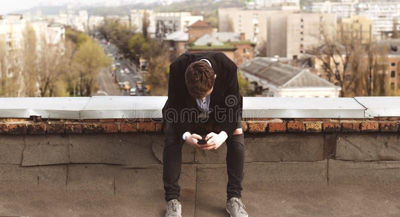 Ung man med en telefon på taket av en byggnad royaltyfria foton