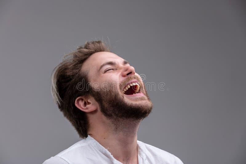 Ung man med ett sinne för humor som tycker om ett skratt fotografering för bildbyråer