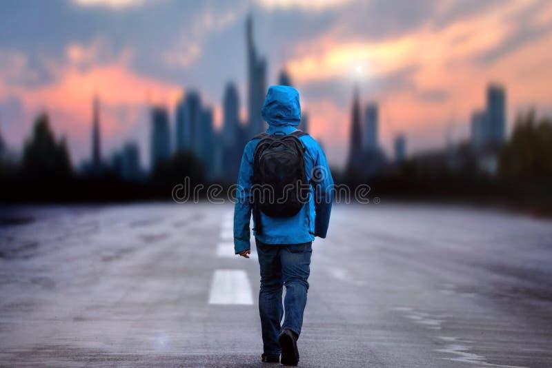 Ung man med ett utomhus- omslag som går in mot en stadssolnedgång arkivfoton