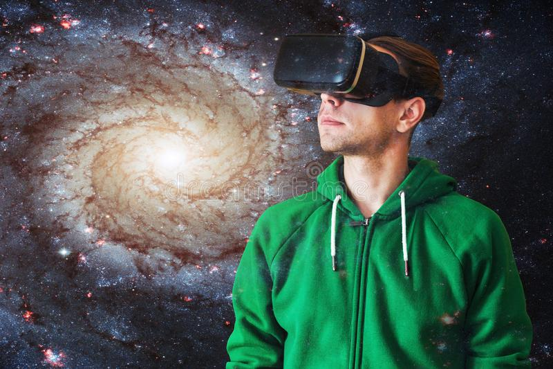 Ung man med exponeringsglas av virtuell verklighet på en bakgrund av galaxen royaltyfria bilder