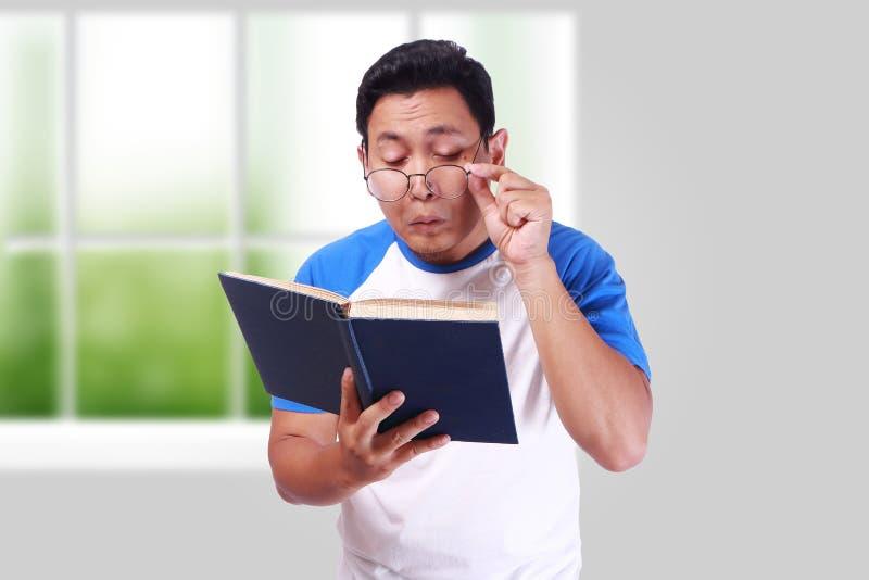 Ung man med exponeringsglas som har dålig vision när läsebok fotografering för bildbyråer