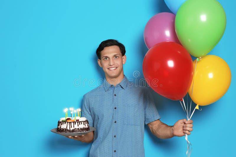 Ung man med födelsedagkakan och ballonger på färgbakgrund arkivbild