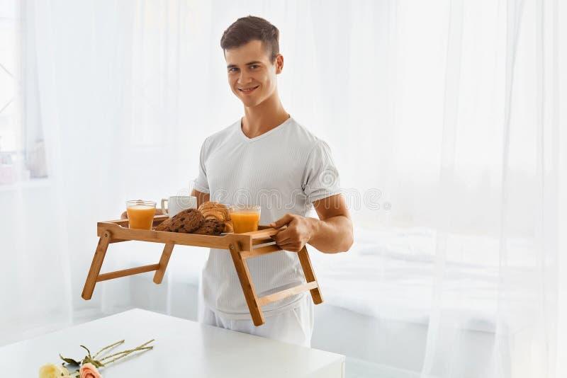 Ung man med frukosten i säng royaltyfria bilder