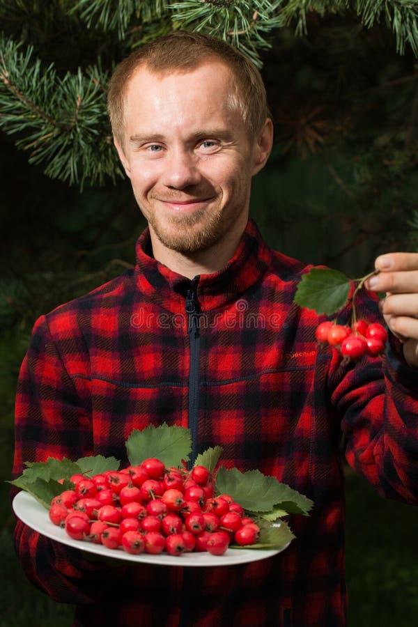 Ung man med frukten av hagtorn royaltyfri bild