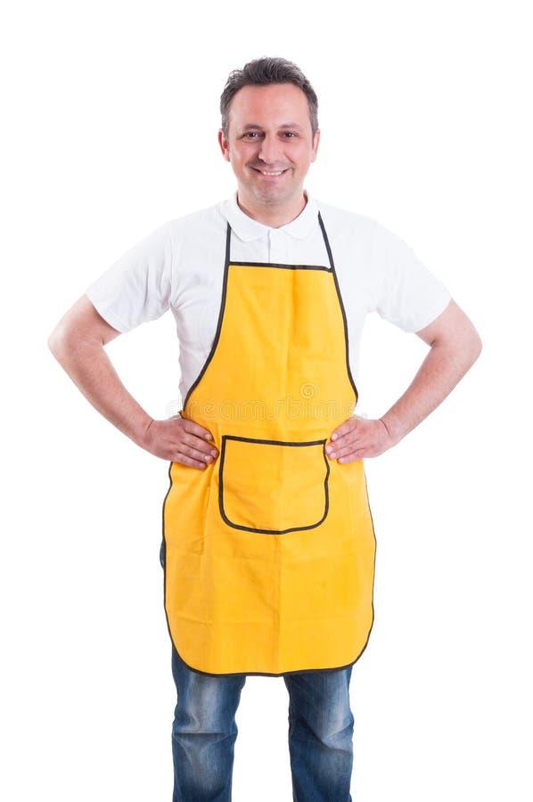 Ung man med gult posera för förkläde som är säkert royaltyfria foton