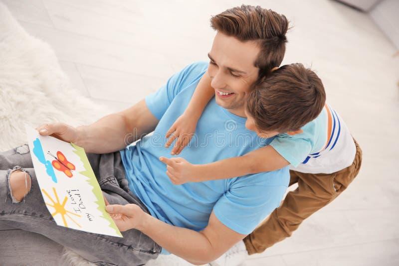 Ung man med hälsningkortet för dag för fader` s arkivfoton