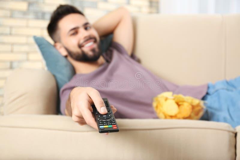 Ung man med hållande ögonen på TV för fjärrkontroll på soffan hemma, fokus royaltyfri fotografi