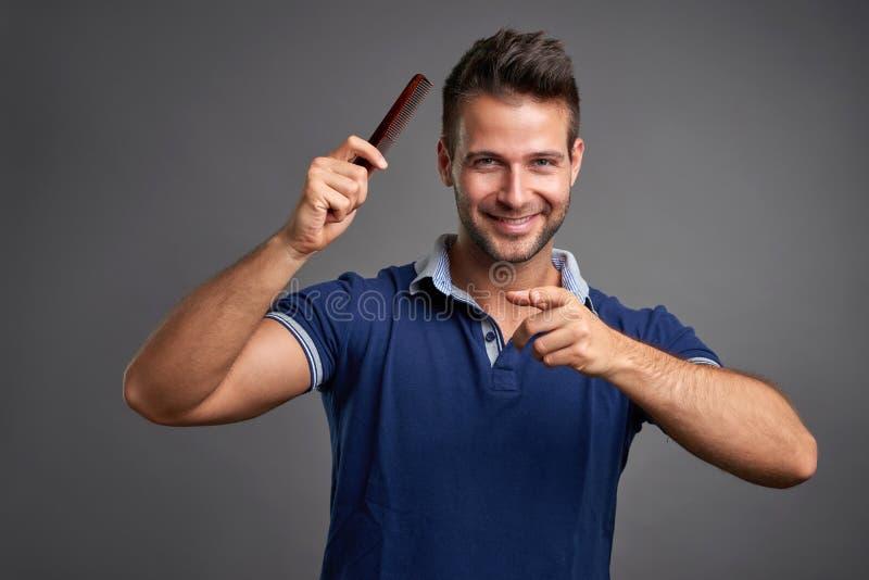 Ung man med hårkammen royaltyfria bilder
