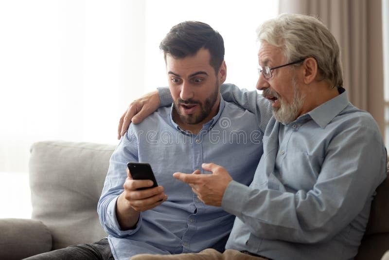 Ung man med h?g fader chockad l?sande nyheterna p? smartphonen royaltyfri foto
