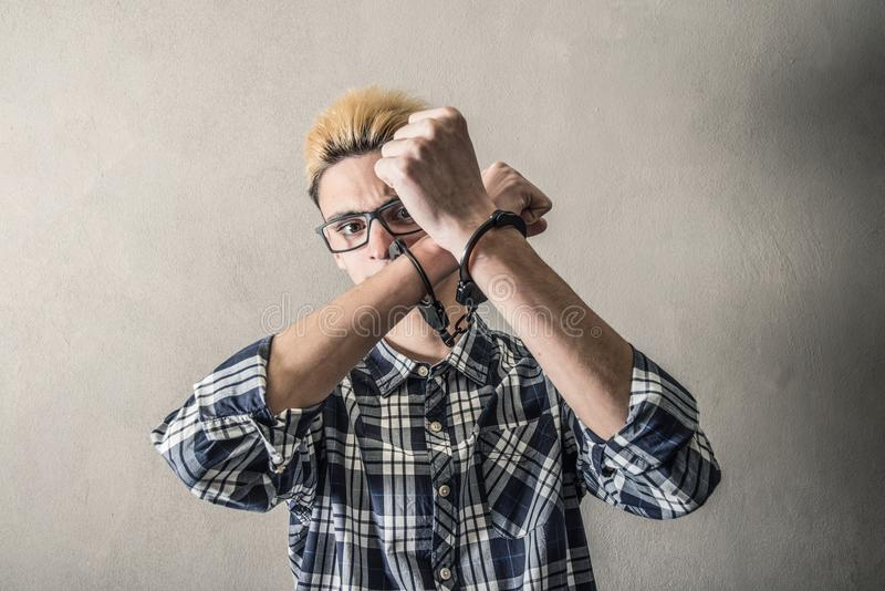 Ung man med handbojor på handlederna royaltyfria bilder