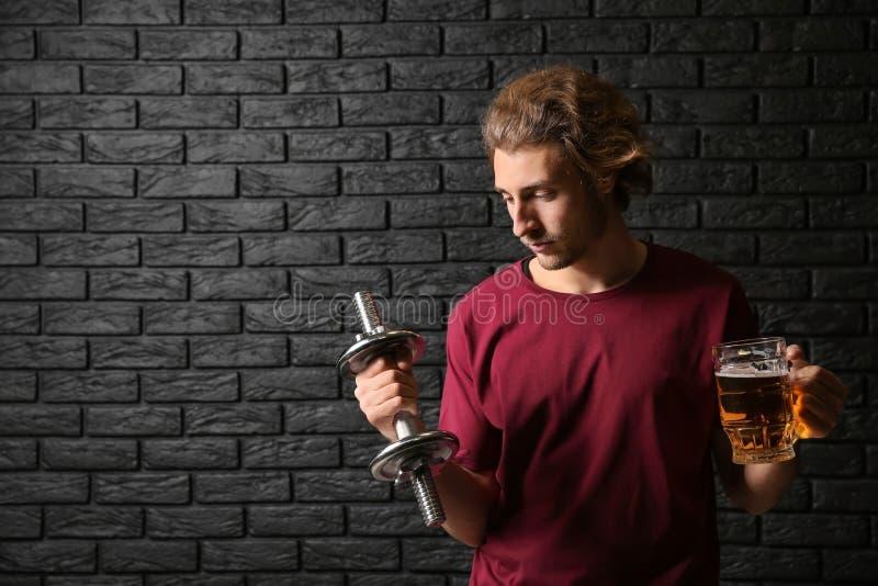 Ung man med hanteln och att råna av öl nära den svarta tegelstenväggen Begrepp av valet mellan alkohol och sporten royaltyfri bild