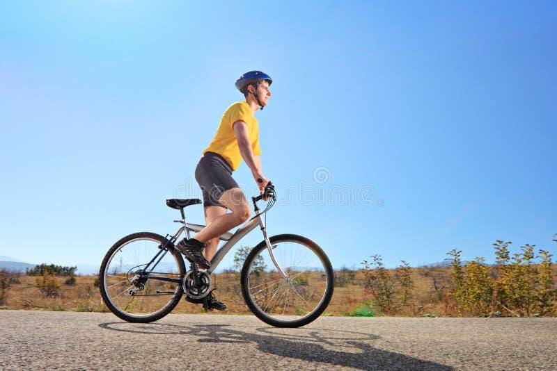 Ung man med hjälmen som rider en cykel på en solig dag royaltyfria bilder