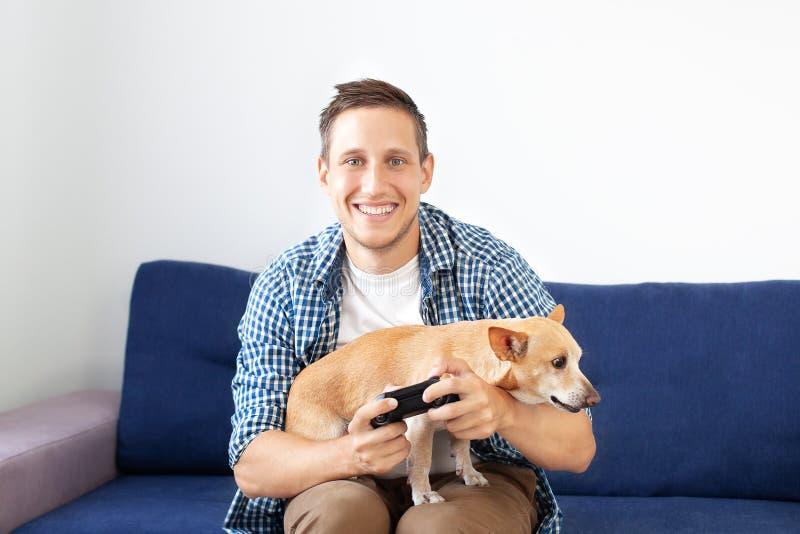 Ung man med hunden som sitter på soffan och rymmer styrspaken Närbild av en attraktiv borstgrabb som rymmer en styrspak som spela royaltyfri foto