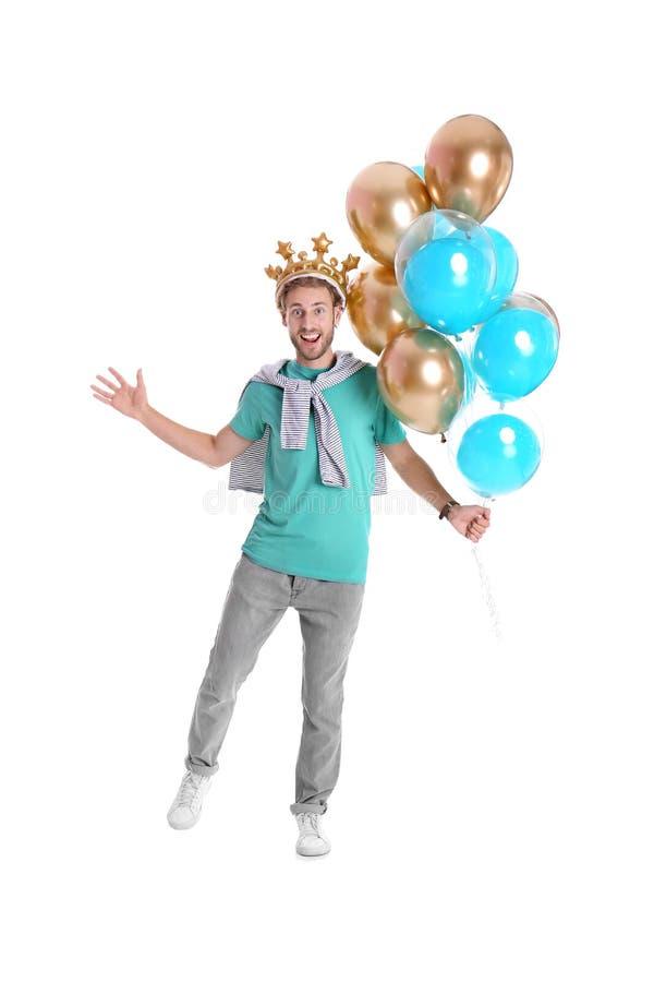 Ung man med krona- och luftballonger royaltyfri fotografi