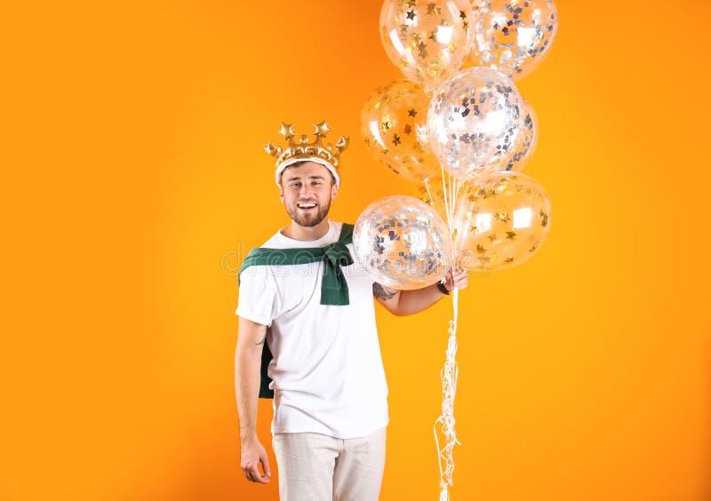 Ung man med krona- och luftballonger fotografering för bildbyråer