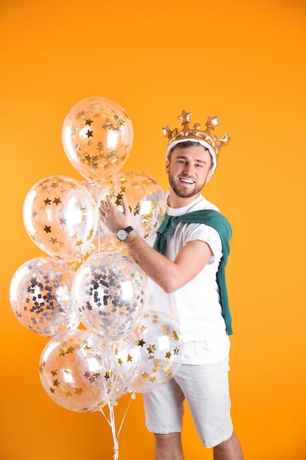 Ung man med krona- och luftballonger arkivfoton
