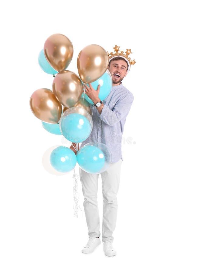 Ung man med krona- och luftballonger royaltyfria bilder