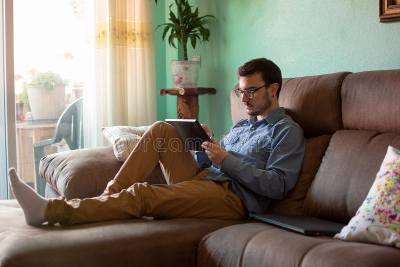 Ung man med minnestavlan p? soffan hemma royaltyfri foto