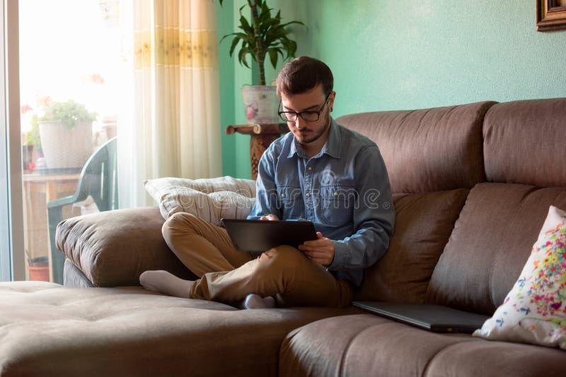 Ung man med minnestavlan p? soffan hemma arkivfoton