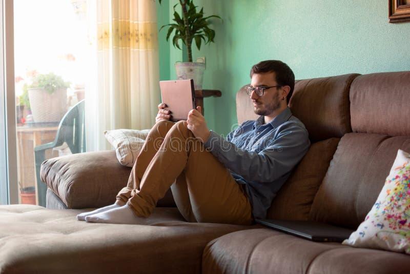Ung man med minnestavlan p? soffan hemma royaltyfria bilder