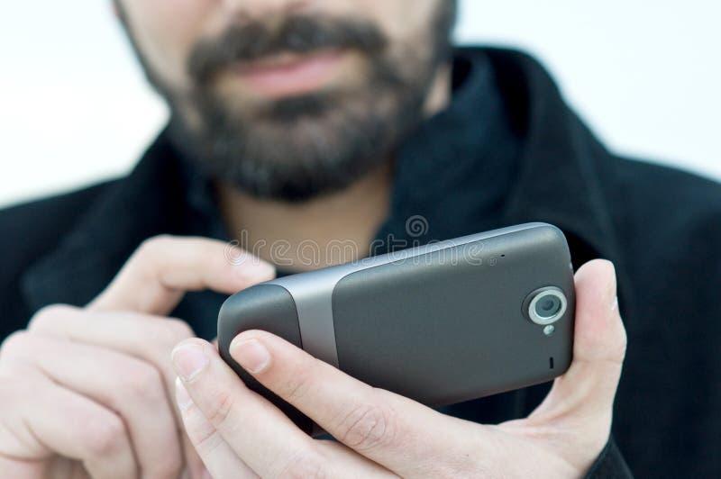 Ung man med mobiltelefonen royaltyfri fotografi