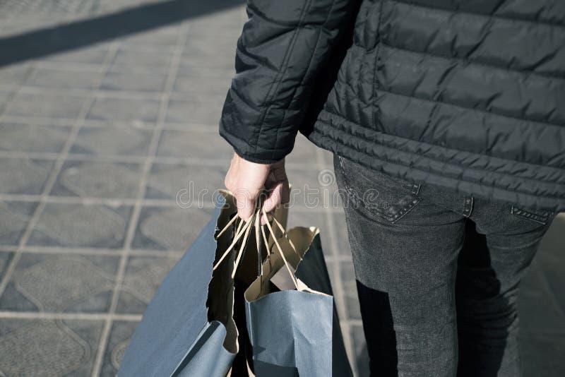 Ung man med några shoppingpåsar på gatan royaltyfria bilder