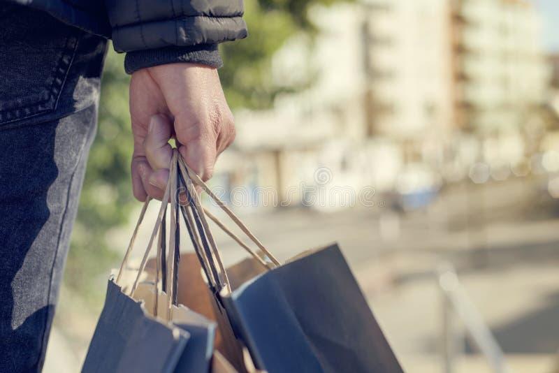 Ung man med några shoppingpåsar på gatan arkivfoto