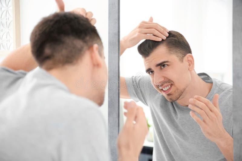 Ung man med problemet för hårförlust som ser i spegel arkivfoton