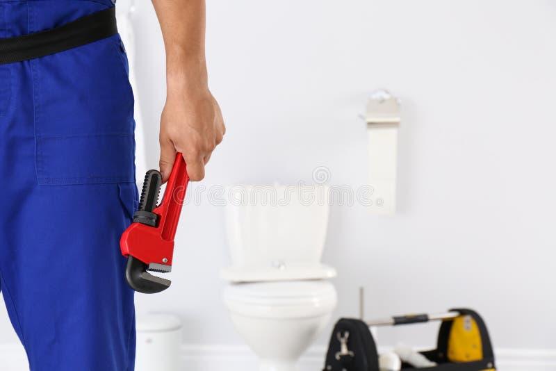 Ung man med rörmokareskiftnyckeln och toalettbunken arkivbilder
