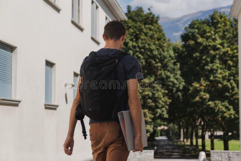 Ung man med ryggsäcken som går till skola efter sommarferier fotografering för bildbyråer