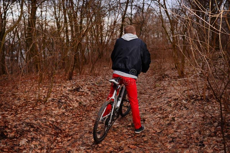 Ung man med ryggsäckridningcykeln på bergvägen i skogen arkivfoton
