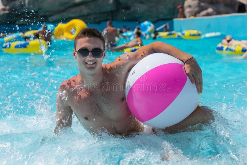 Ung man med simbassängen för strandboll offentligt arkivfoto