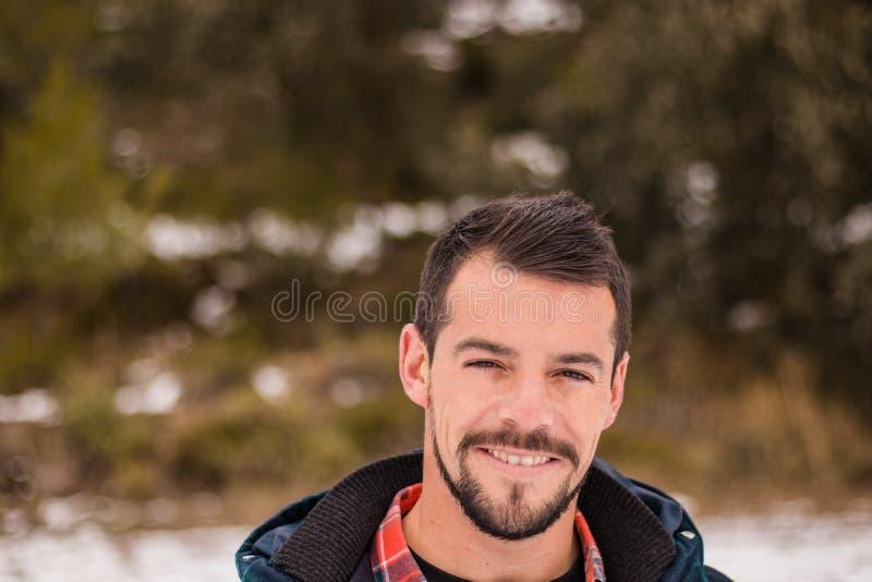 Ung man med skägget som skrattar i natur arkivfoton