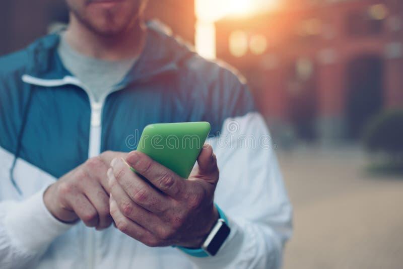 Ung man med smarta klockor som skriver på hans mobiltelefon, solnedgång på gatan royaltyfri bild