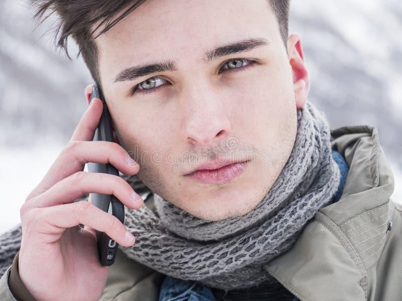 Ung man med smartphonen i snö royaltyfri foto