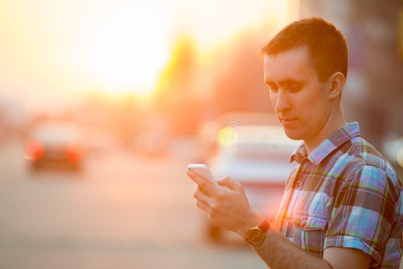 Ung man med smartphonen på den soliga gatan royaltyfri foto