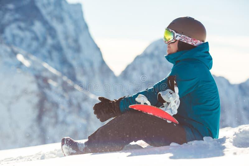 Ung man med snowboarden i händer arkivbilder
