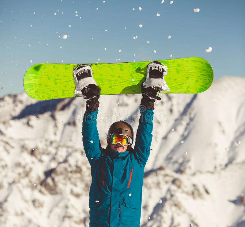 Ung man med snowboarden i händer royaltyfria bilder
