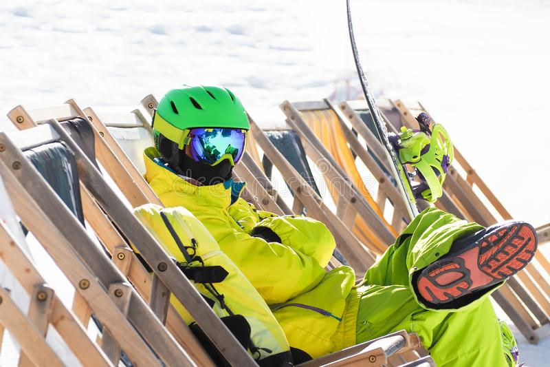 Ung man med snowboarden som sitter och kopplar av fotografering för bildbyråer