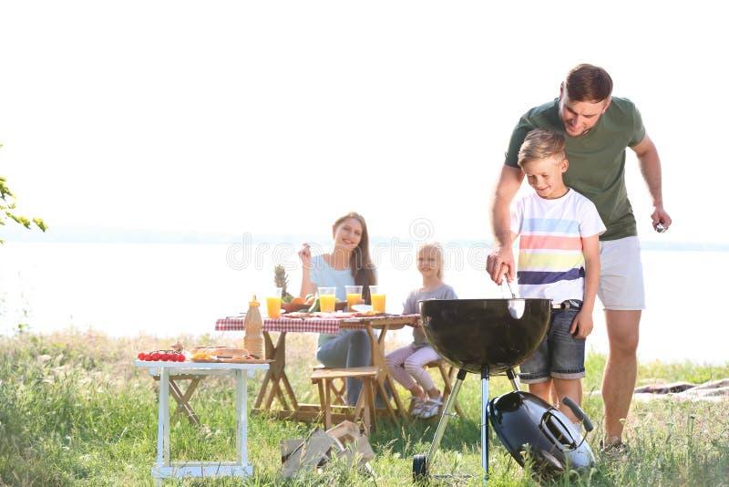 Ung man med sonen som utomhus lagar mat smaklig mat på grillfestgaller Familj av fyra i h?stskogen royaltyfri foto