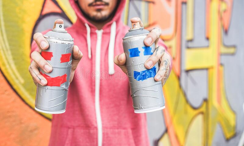 Ung man med två leende sprejer - Graffiti-målning med aerosolfärgburkar på väggen - Urban-livsstil, ungdom royaltyfri foto