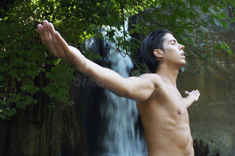 Ung man med utsträckt meditera för armar mot vattenfallet royaltyfri bild