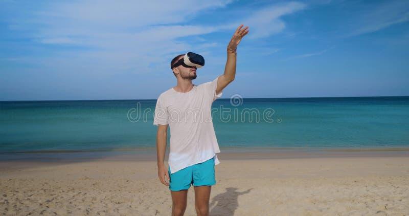 Ung man med virtuell verklighetexponeringsglas på stranden royaltyfria foton