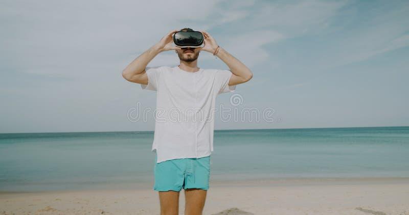 Ung man med virtuell verklighetexponeringsglas på stranden arkivfoton