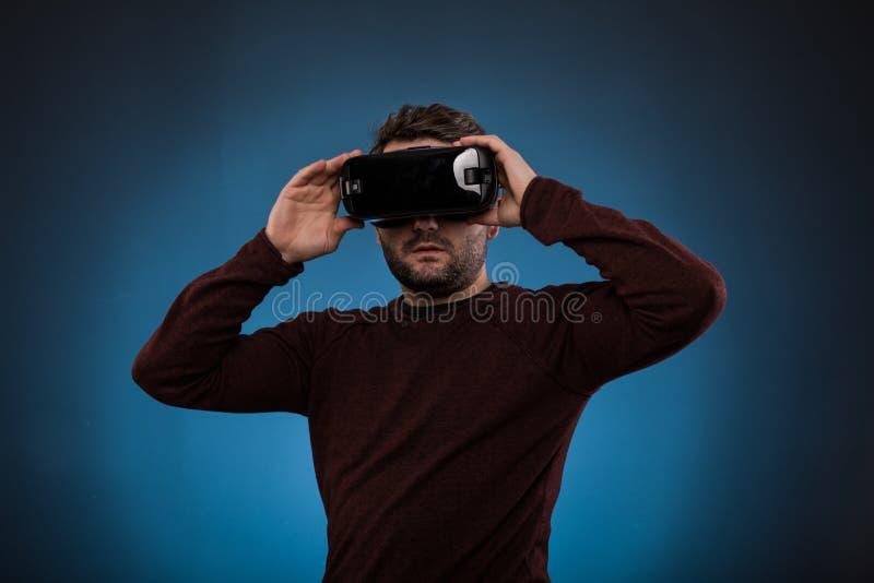 Ung man med virtuell verklighethörlurar med mikrofon eller exponeringsglas 3d över blått arkivbilder