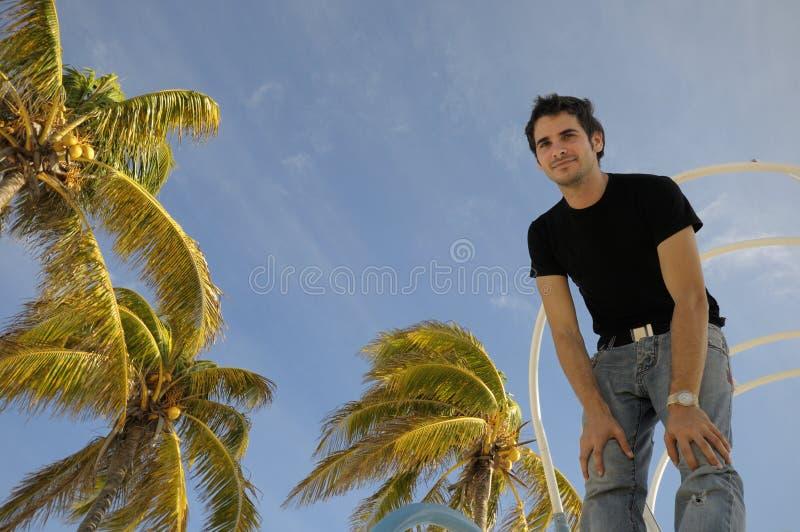 Ung man mot den tropiska skyen royaltyfria bilder